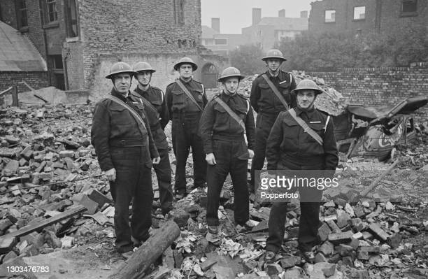 Wardens from an Air Raid rescue squad pose together on a bomb site, created by German Luftwaffe air raids in the Liverpool Blitz, in Liverpool,...
