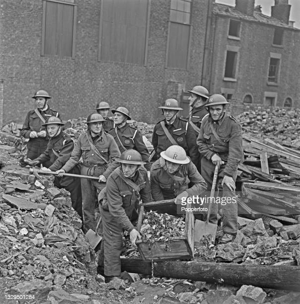 Wardens from an Air Raid rescue squad work together to clear a bomb site, created by German Luftwaffe air raids in the Liverpool Blitz, on a...