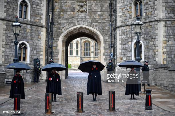 Wardens of the Castle shelter from the rain beneath umbrellas outside Windsor Castle in Windsor, west of London, on April 10 the day after the death...