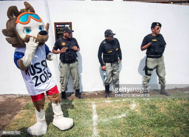 Wardens stand guard next to a person dressed as the World Cup official mascot Zabivaka the Wolf during a First Interprison World Cup Russia 2018...