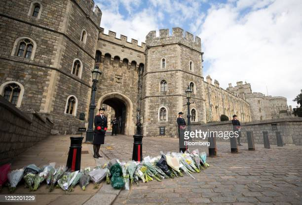 Wardens stand next to flower tributes to Prince Philip, Duke of Edinburgh, outside the entrance to Windsor Castle in Windsor, U.K., on Friday, April...