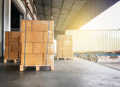 Warehouse cargo courier shipment. Stack of cardboard boxes on wooden pallet and truck docking at warehouse 1159935084