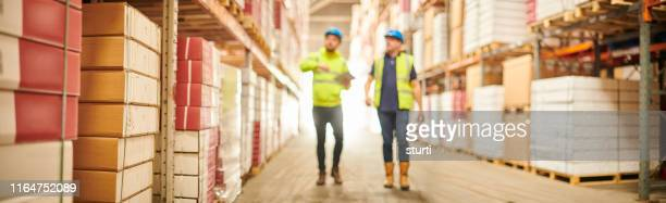 warehouse copy space with blurred workers - freight transportation stock pictures, royalty-free photos & images
