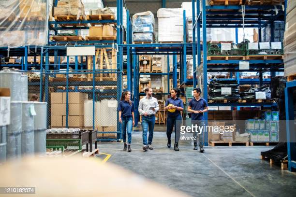 warehouse employees walking through aisle and talking - distribution warehouse stock pictures, royalty-free photos & images