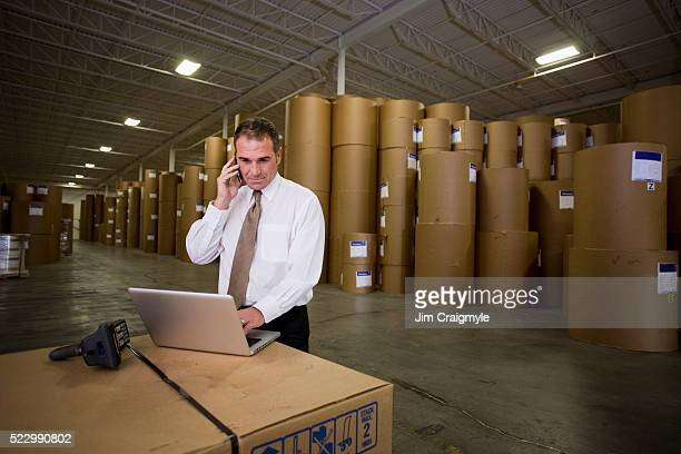 Warehouse foreman talking on a cell phone and using a laptop
