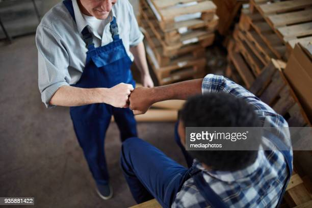 warehouse friends making fist bump - fist bump stock pictures, royalty-free photos & images
