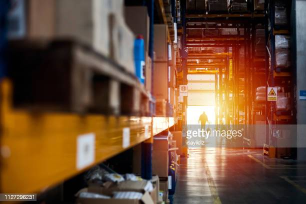 warehouse interior at sunset - warehouse stock pictures, royalty-free photos & images
