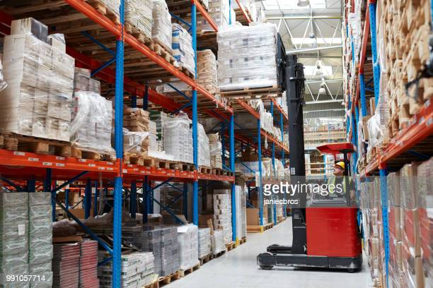 warehouse logistic center. worker driving on a forklift - forklift stock pictures, royalty-free photos & images