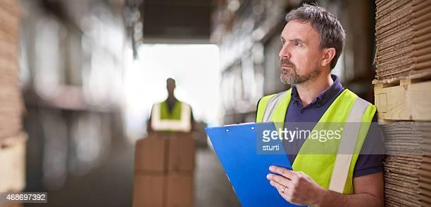 warehouse manager, die auf seinem laptop Lieferungen