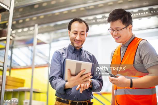 warehouse manager discussing with foreman - foreperson stock pictures, royalty-free photos & images