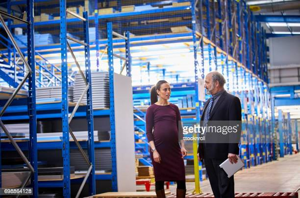 Warehouse manager discussing work with female supervisor