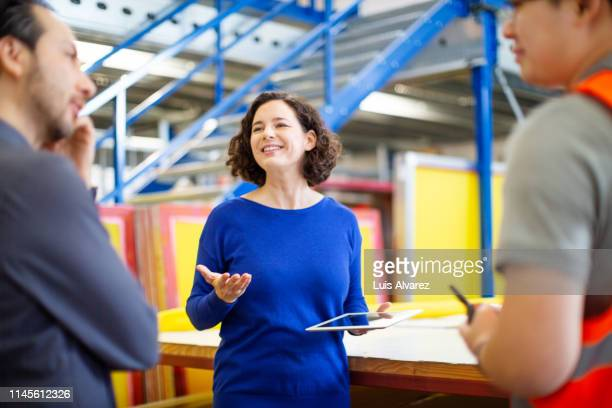 warehouse manager talking with workers - mid section stock photos and pictures
