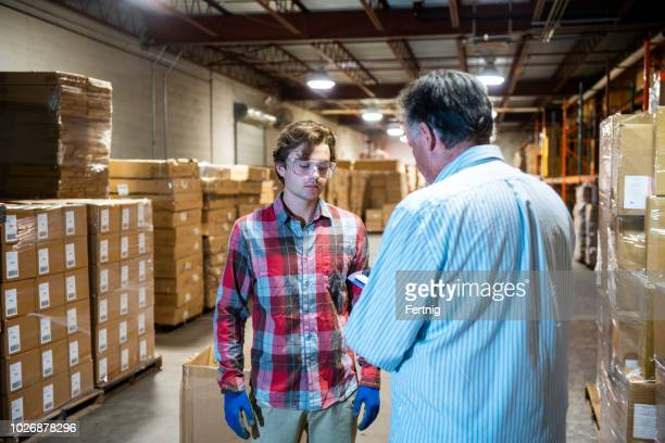 a warehouse manager talks with a younger warehouse worker. - being fired stock photos and pictures