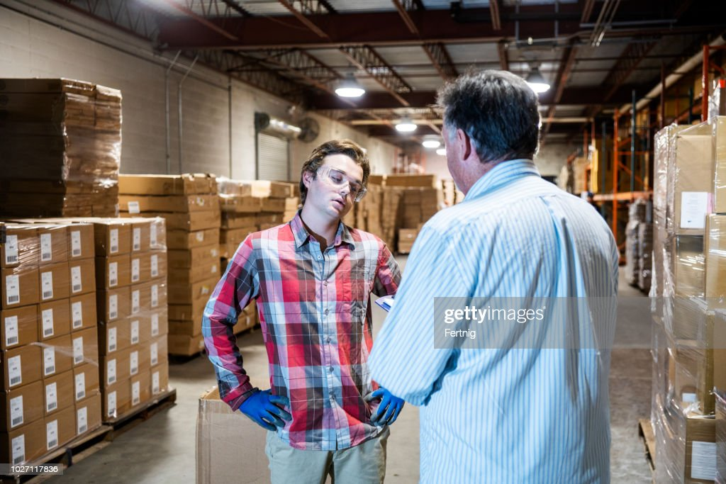 A warehouse manager talks with a younger warehouse worker. : Stock Photo