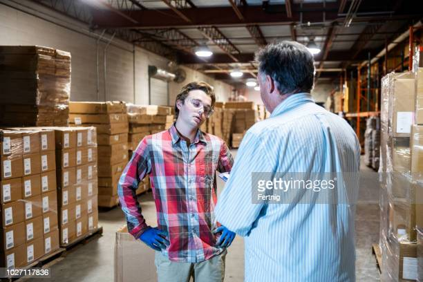 a warehouse manager talks with a younger warehouse worker. - being fired stock pictures, royalty-free photos & images