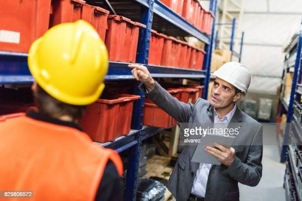 Warehouse manager with worker taking stock