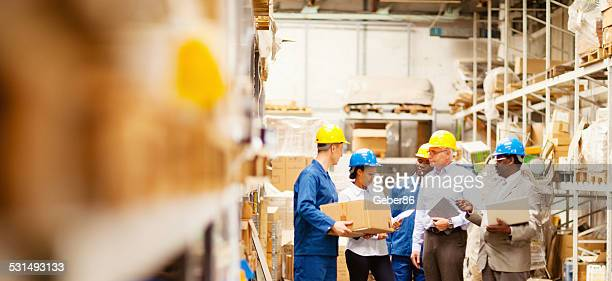 Warehouse managers talking to workers