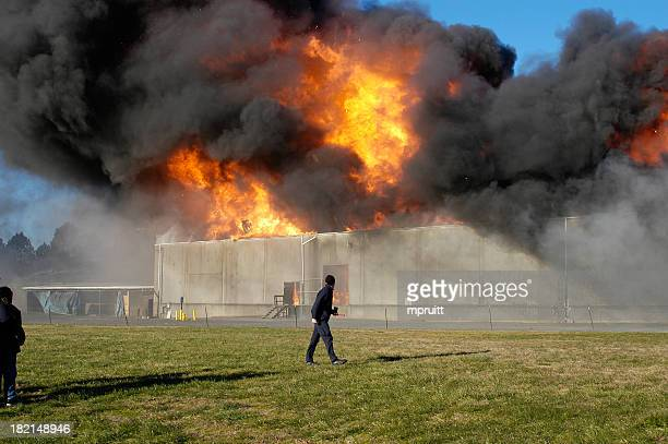 Warehouse on fire releasing think black smoke to the sky