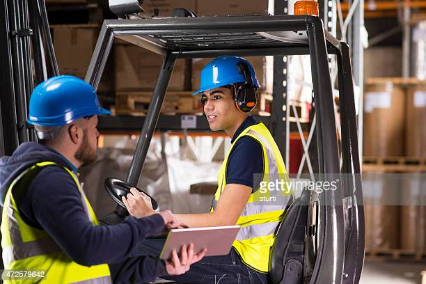 warehouse supervisor chats to young forklift truck driver trainee