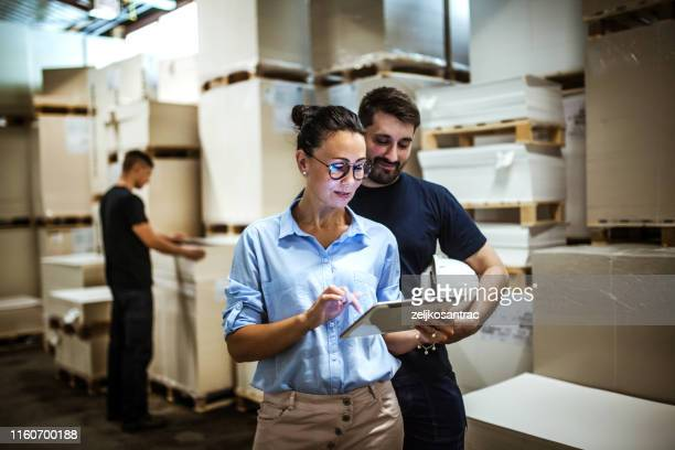 warehouse supervisor walking and talking with senior manager - science and technology stock pictures, royalty-free photos & images
