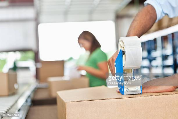 warehouse worker assembling packages in assembly line - tape dispenser stock photos and pictures
