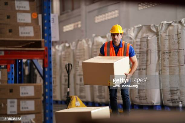 warehouse worker carry merchandise box to pallet truck at storage compartment - luggage hold stock pictures, royalty-free photos & images