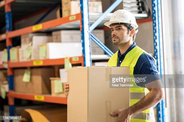 warehouse worker carrying goods in cardboard box. courier collecting or delivering parcel business. - health and safety stock pictures, royalty-free photos & images