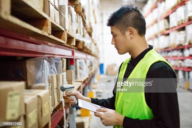 warehouse worker checking cargo on shelves with scanner - bar code stock pictures, royalty-free photos & images