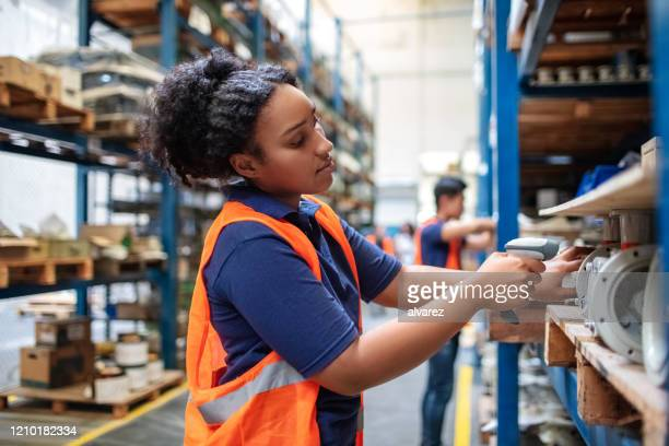 warehouse worker checking cargo on shelves with scanner - packaging stock pictures, royalty-free photos & images