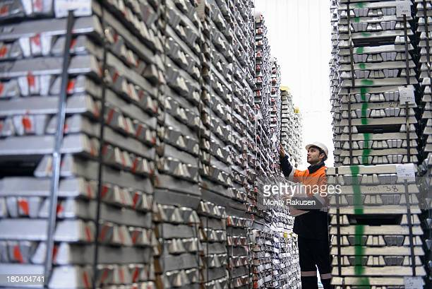 Warehouse worker checking stacked aluminum ingots