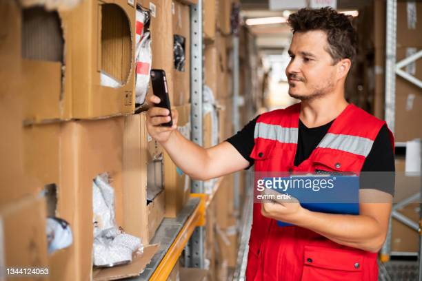 warehouse worker controlling the orders with smartphone - luggage hold stock pictures, royalty-free photos & images