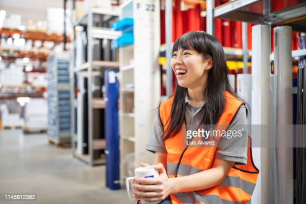 warehouse worker during a coffee break - coffee break stock pictures, royalty-free photos & images