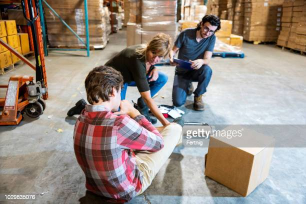 a warehouse worker fallen after tripping on some debris.  he is clutching his ankle in pain as two supervisors assists him. - first aid kit stock pictures, royalty-free photos & images