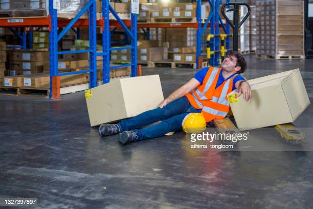 a warehouse worker has an accident at work. - luggage hold stock pictures, royalty-free photos & images