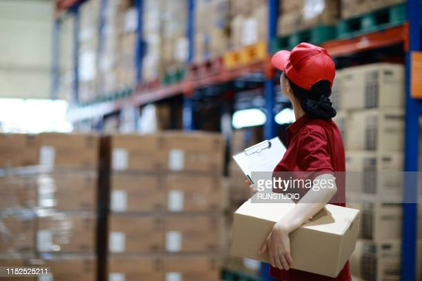 warehouse worker holding cardboard box in logistics warehouse - 貯蔵庫 ストックフォトと画像