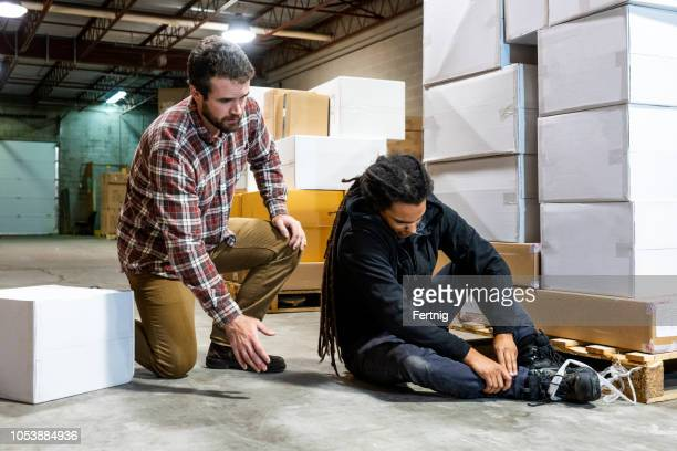 a warehouse worker hurt after falling beside a pallet - injured stock pictures, royalty-free photos & images