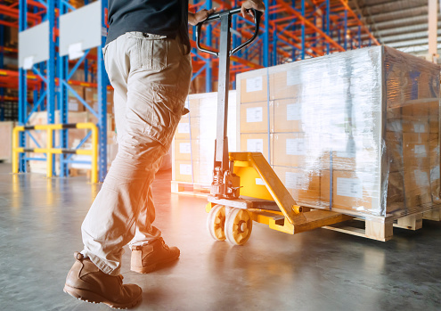 Warehouse worker is working with hand pallet truck and cargo pallet 1157049071