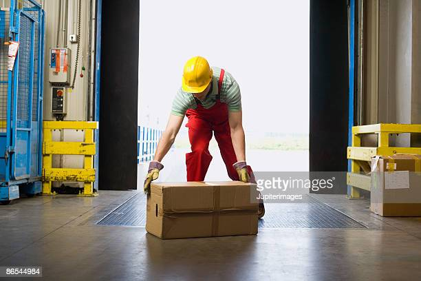 warehouse worker lifting box - bending over stock pictures, royalty-free photos & images