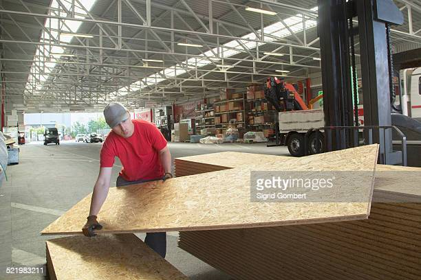 warehouse worker lifting wooden boards in hardware store warehouse - sigrid gombert stock pictures, royalty-free photos & images