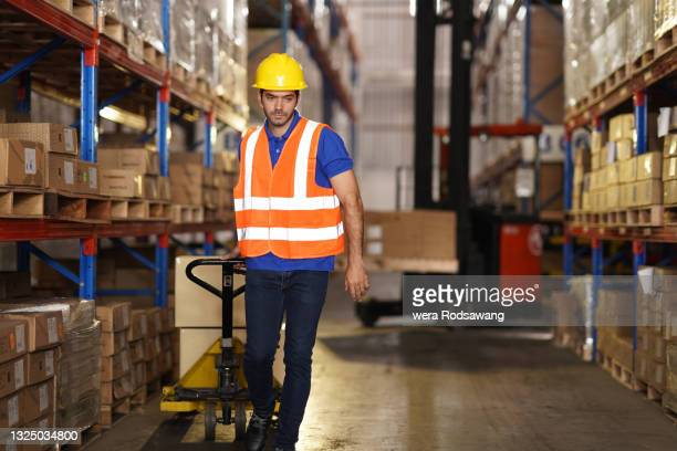 warehouse worker pulling a pallet truck with cardboard-boxes delivery to storage shelf - luggage hold stock pictures, royalty-free photos & images