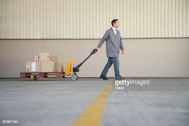 Warehouse worker pulling handtruck