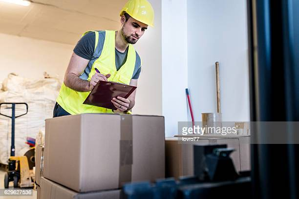 Warehouse worker reviewing a new shipment of material