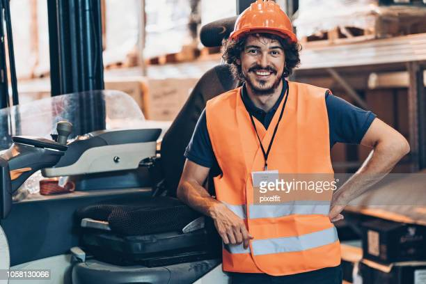 Warehouse worker standing next to a forklift