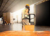 Warehouse worker unloading pallet shipment goods into a truck container