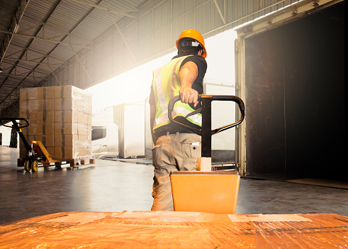 Warehouse worker unloading pallet shipment goods into a truck container 1195392846