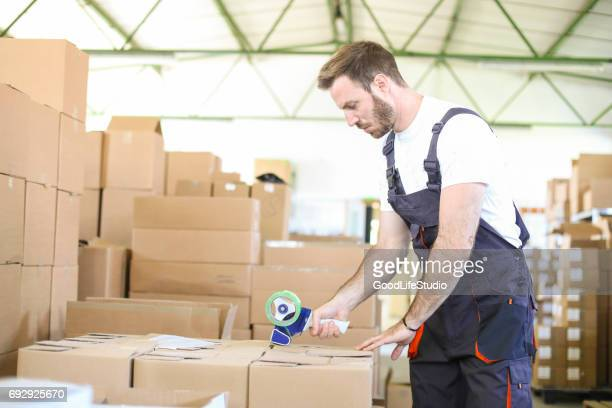 warehouse worker using a tape dispenser - tape dispenser stock photos and pictures
