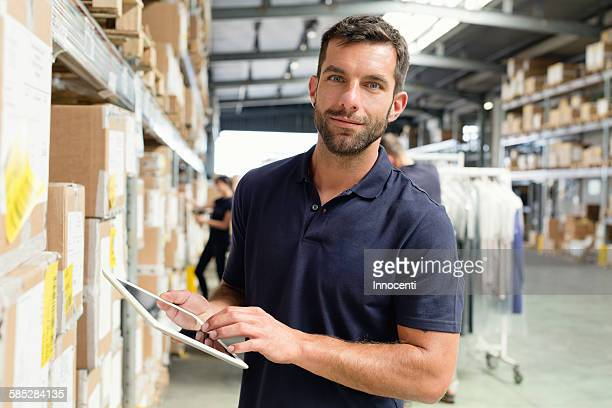 Warehouse worker using digital tablet in distribution warehouse