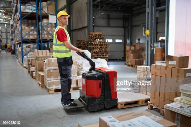 Warehouse worker walking among shelves with handcart