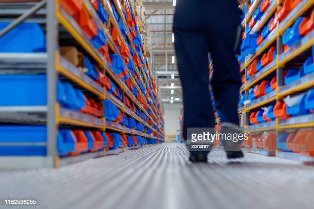 warehouse worker walking between aisles - industrial storage bins stock pictures, royalty-free photos & images