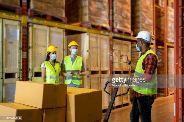 warehouse worker wearing protective mask to protect against covid-19 - health and safety stock pictures, royalty-free photos & images